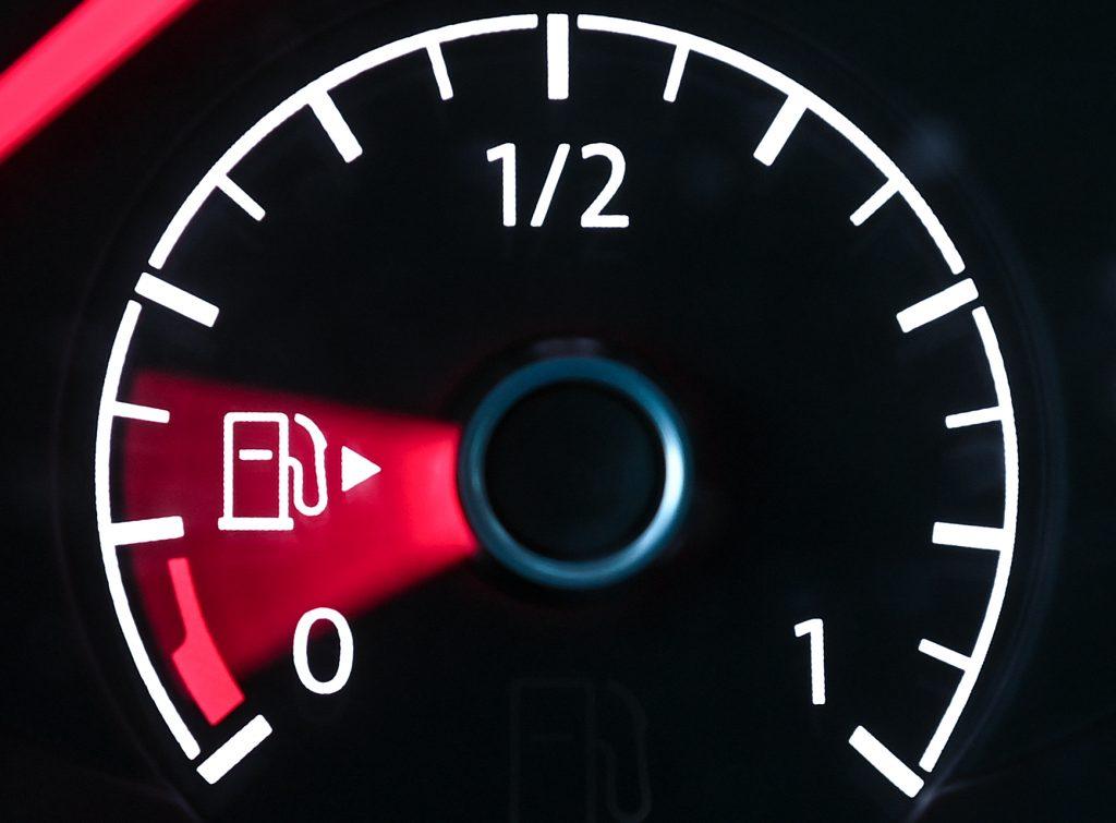 A car's fuel gauge points toward empty