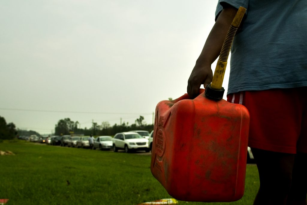 A person carrying a red plastic gas can on the side of the road
