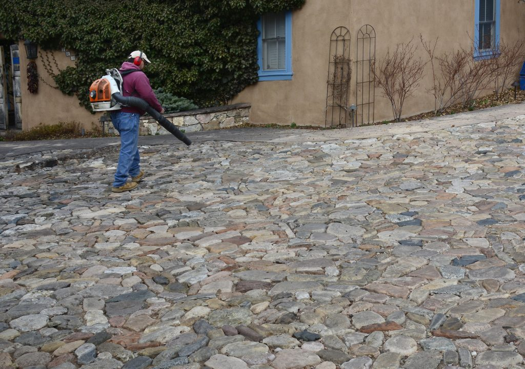 A man uses a gas-powered backpack leaf blower to clean up a yard in Santa Fe, New Mexico