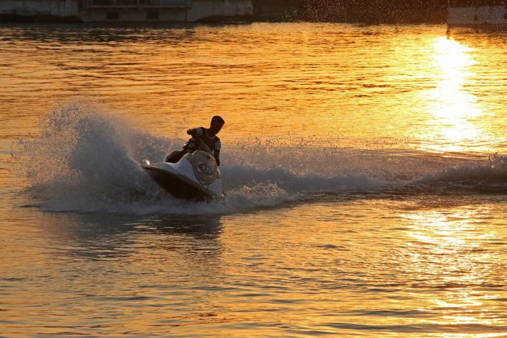 A person rides a jet ski on a river at sunset