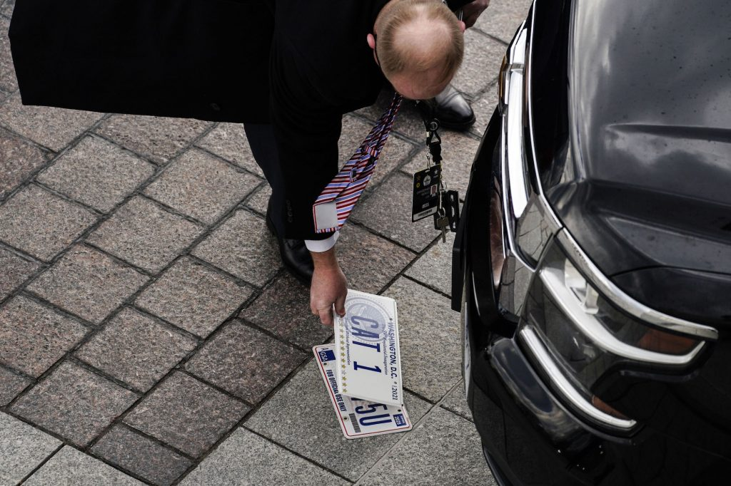 Officials transfer license plates of the motorcade ahead of the inauguration of President Joe Biden.
