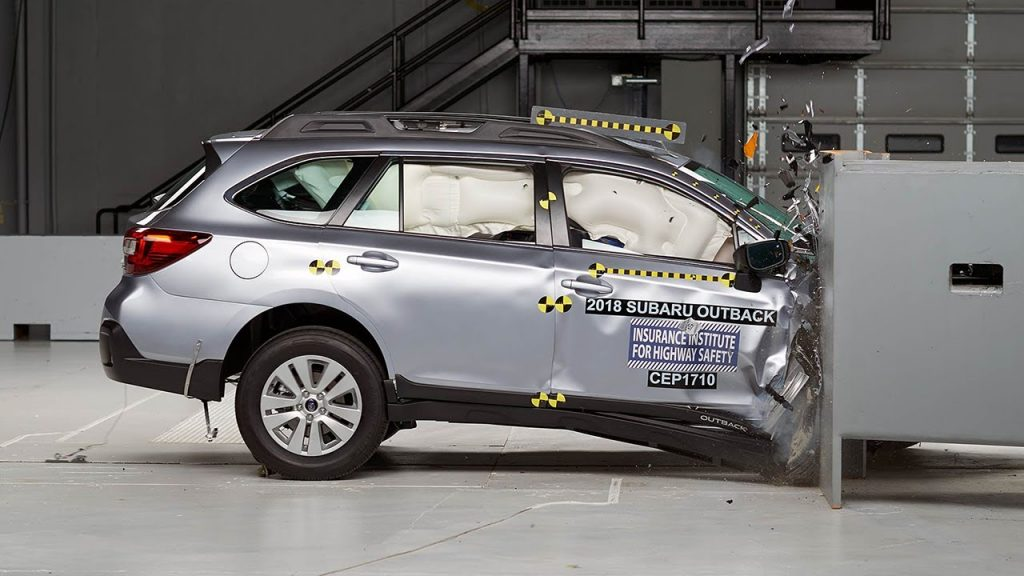 A silver Subaru Outback is crash-tested.