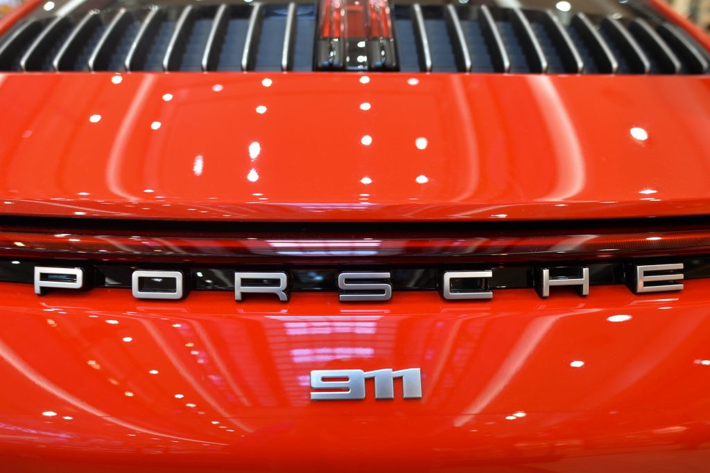 The chrome 911 badging of a red Porsche