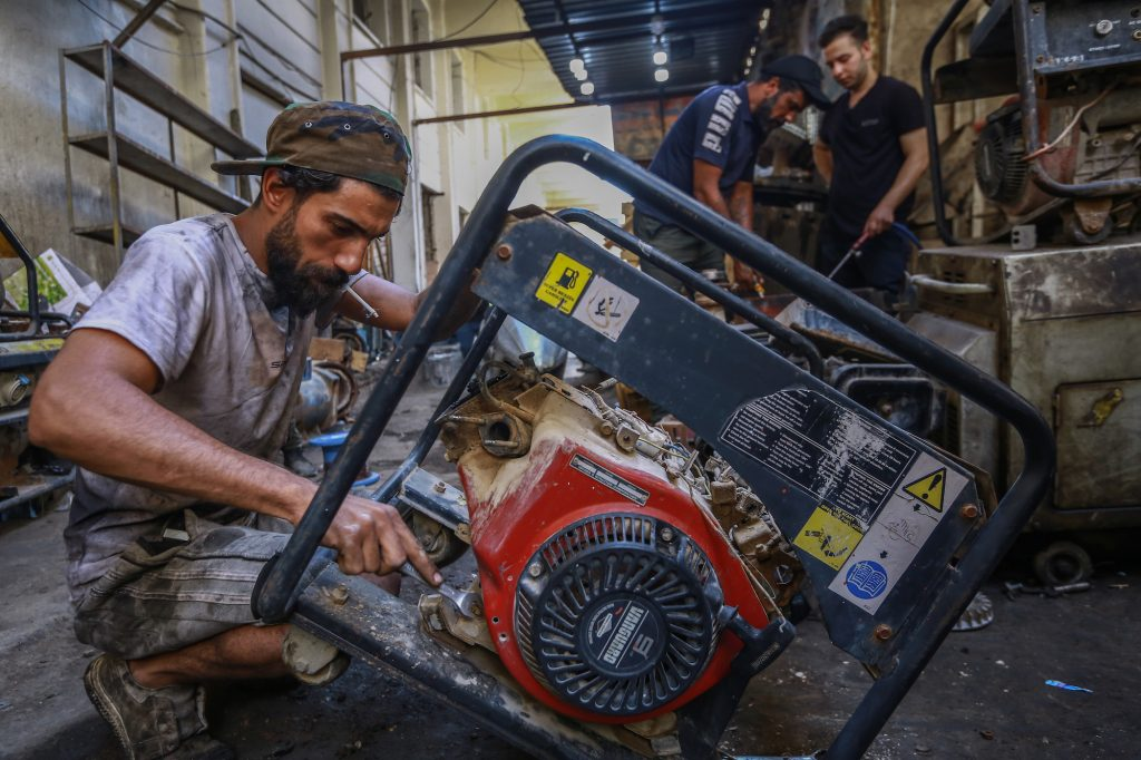 Aworker repairs a portable generator in a workshop