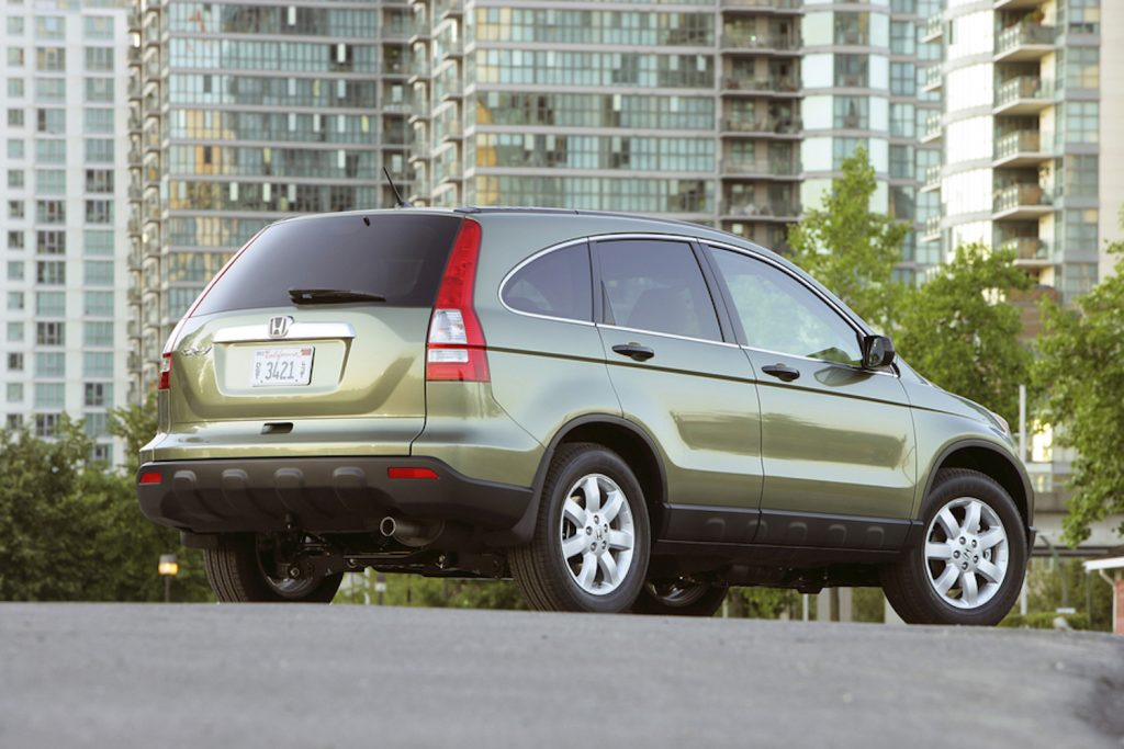 A rear quarter view of a green 2009 Honda CR-V parked in the city.