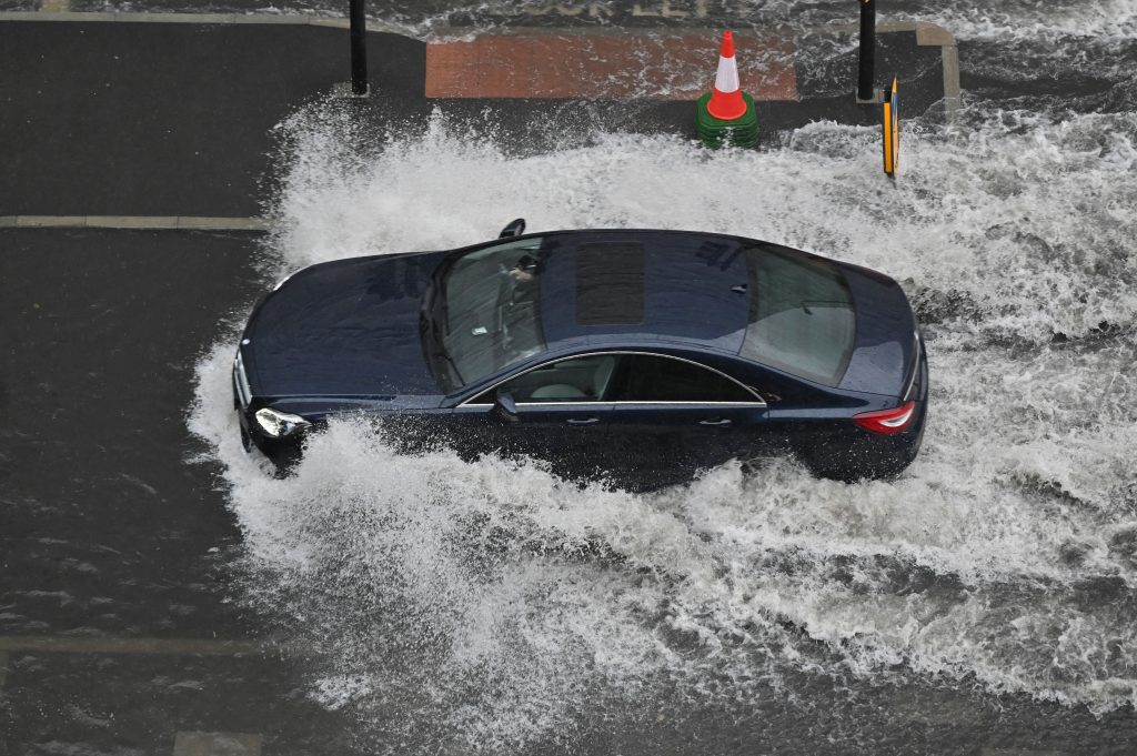 Cars drive through deep water on a flooded road