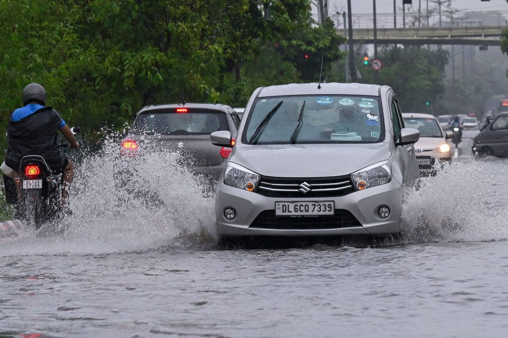 Vehicles drive along a water-logged road during heavy monsoon rains