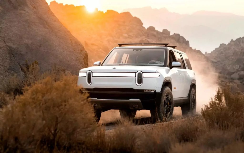 A white Rivian R1S driving through the desert at sunset