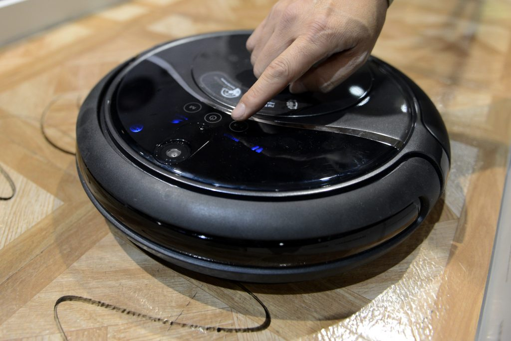 A person's finger presses a button on a robot vaccum cleaner sitting on linoleum