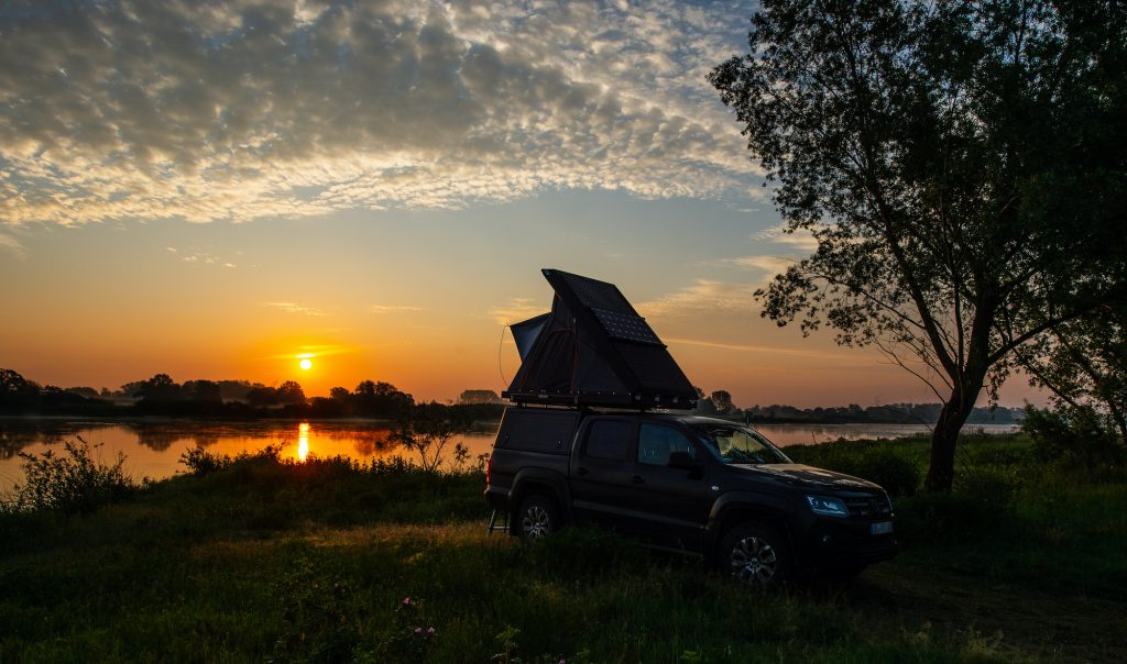 An off-road vehicle with an open roof tent stands on the banks of the Elbe river at sunrise.