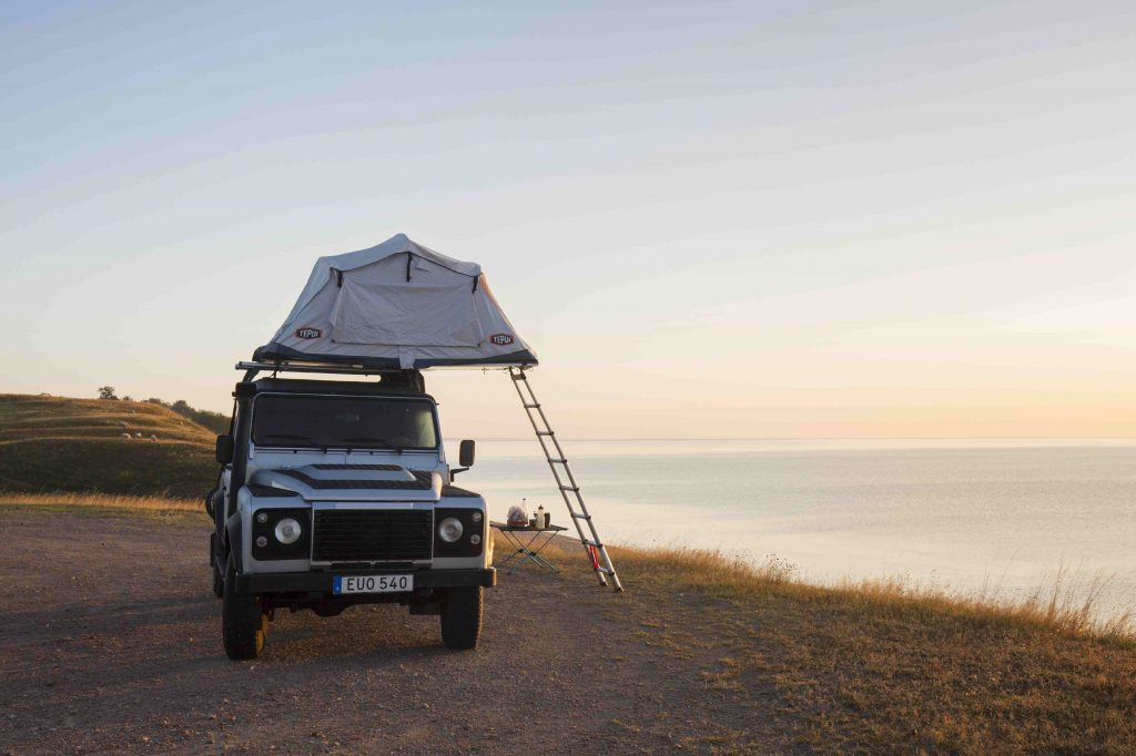 Off-road four-wheel-drive vehicle with rooftop tent camping along the Baltic Sea.