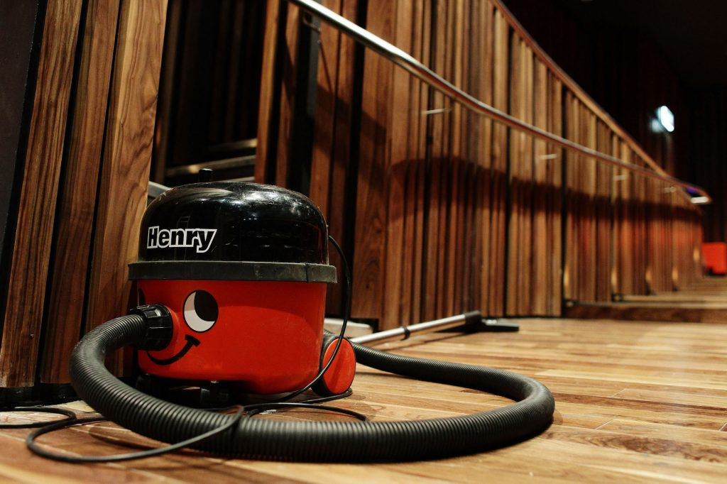 A shop vac sits on a wood floor in a wood-paneled auditorium