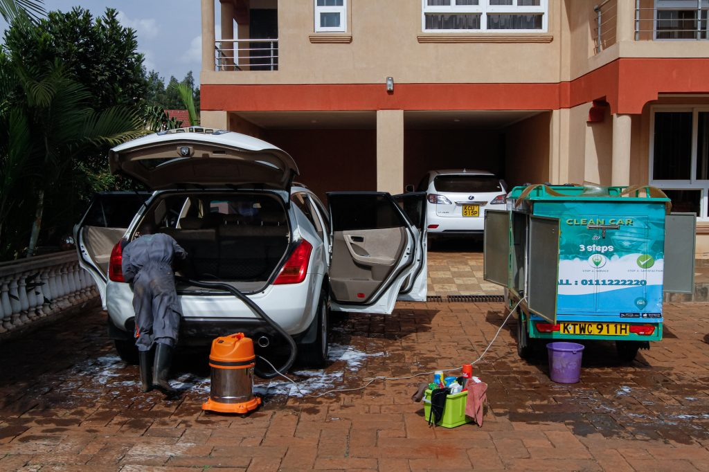 A mobile car wash worker uses a shop vac to vacuum the back of an SUV in a customer's front yard