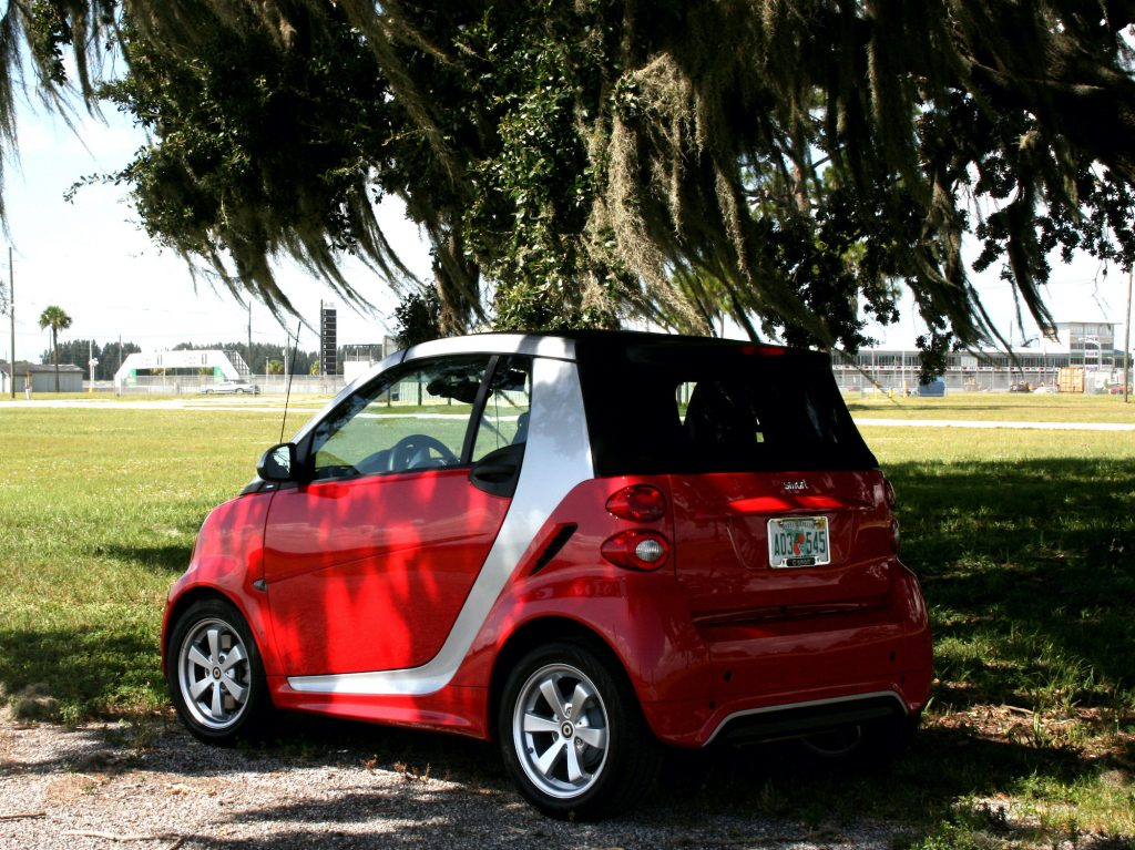 The Smart Car parked in the shade of an oak tree.