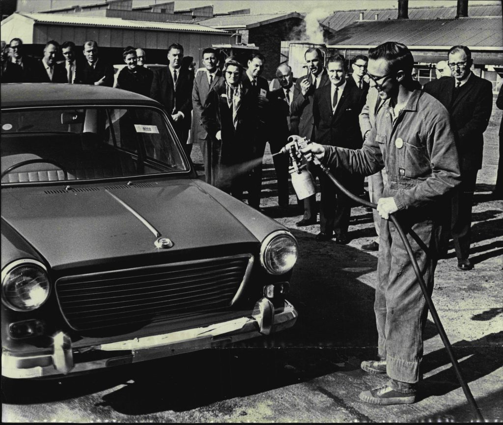 Businesspeople watch a worker use a spray car wax on a vehicle in 1964