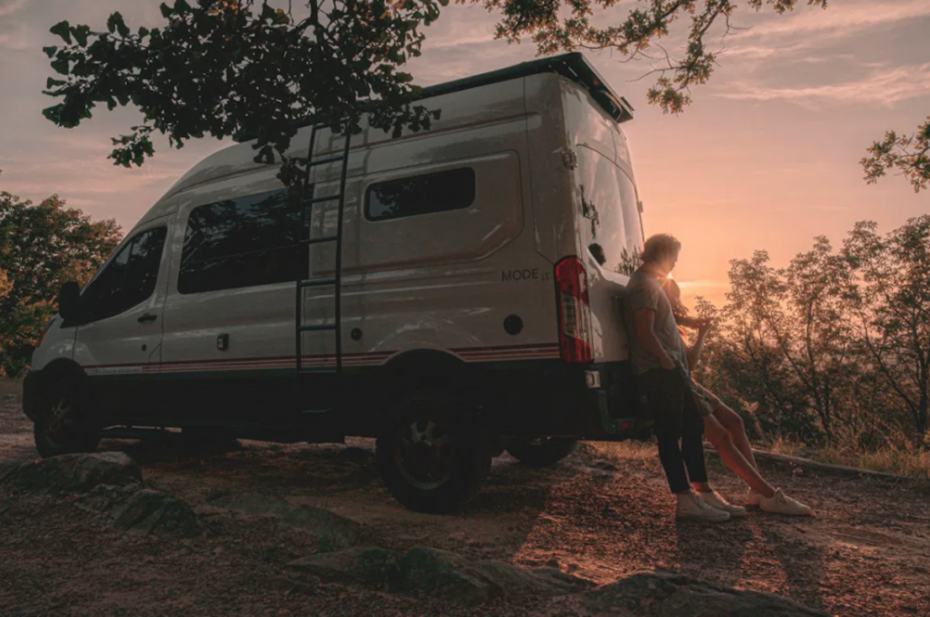 The Alabama made Storytellers 4x4 Camper with a couple leaning against it at sunset