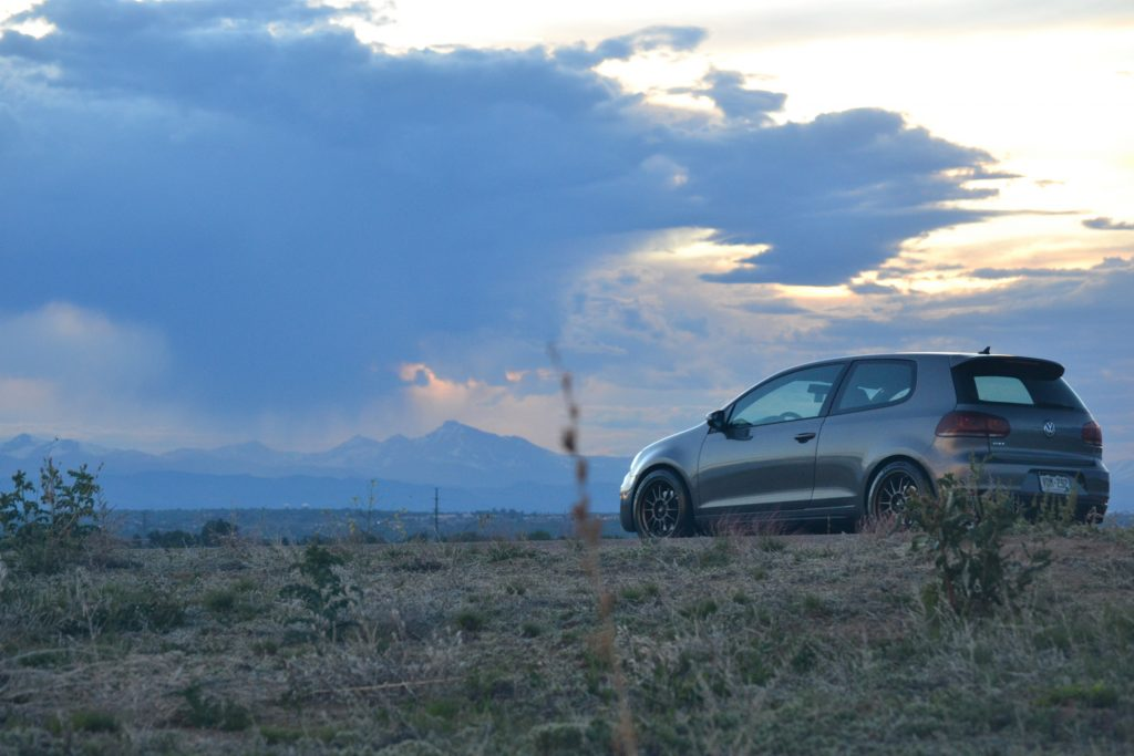 A gray Volkswagen GTI at sunset photographed with the Rocky Mountains in the background