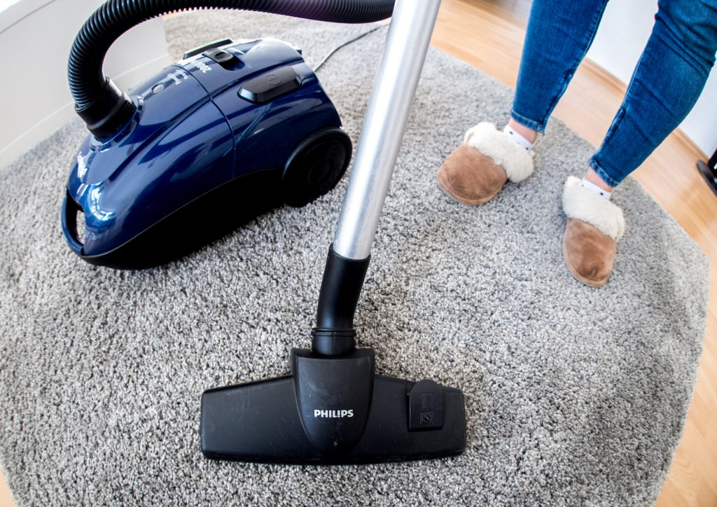 A woman in an apartment uses a vacuum cleaner on carpeting
