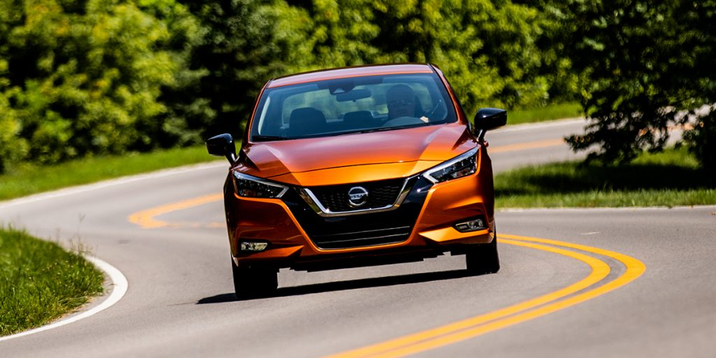 an orange 2021 Nissan Versa driving on a scenic winding road
