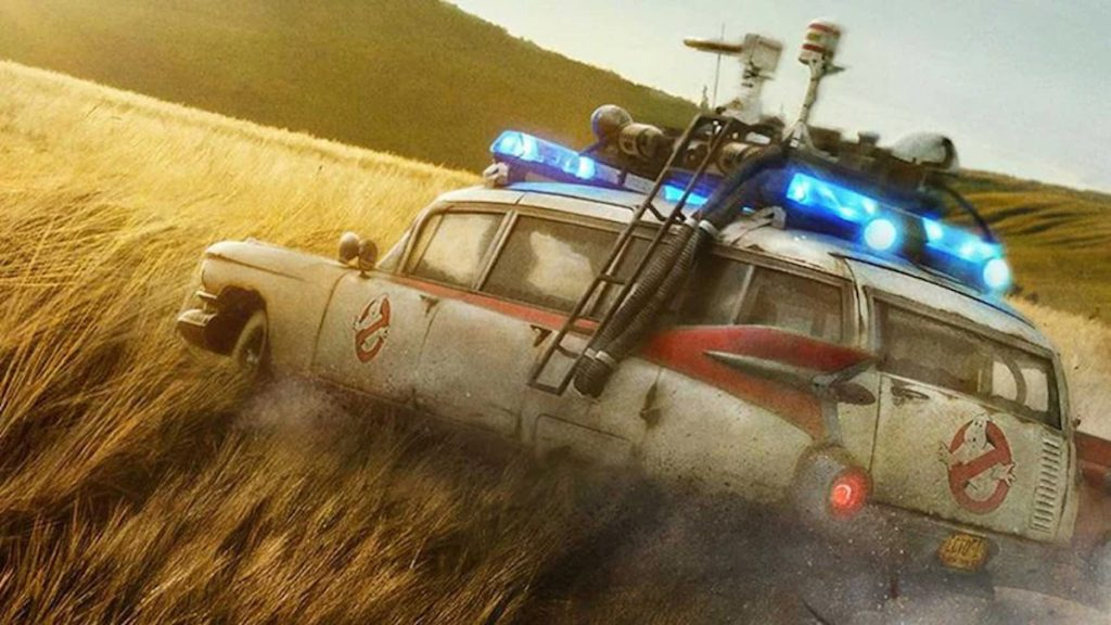 screen shot from the trailer for the new Ghostbuster: Afterlife film showing the Ecto-1 drifting through a barley field