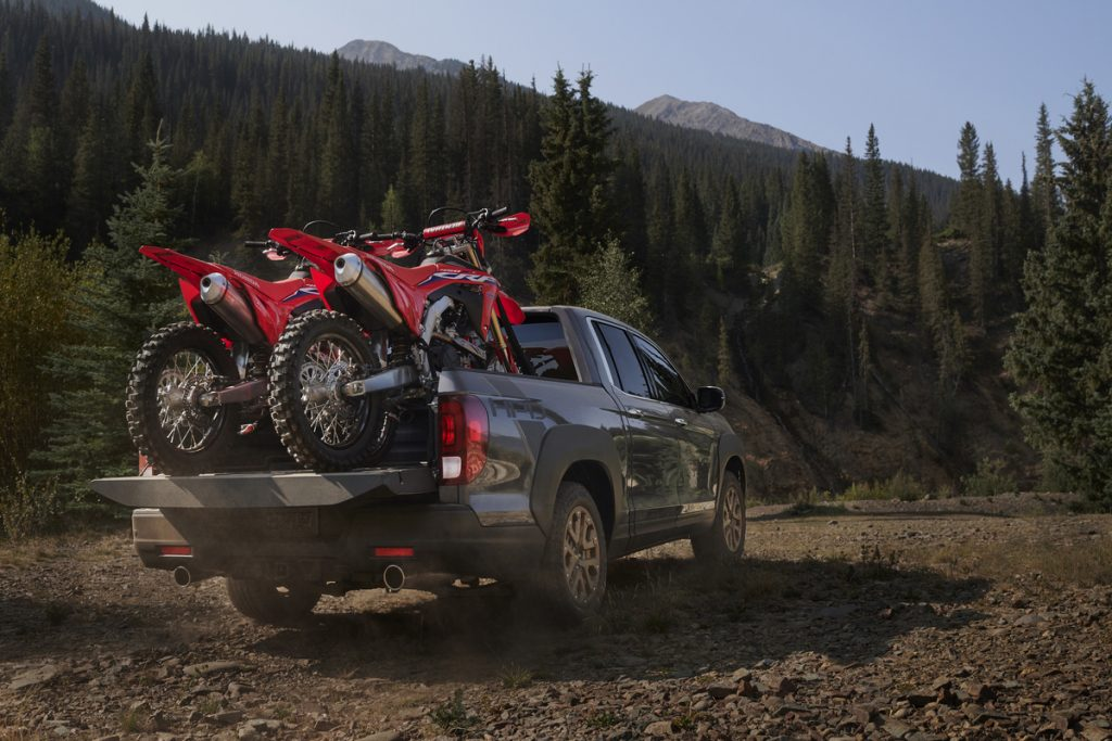 This is a publicity photo of a gray Honda Ridgeline carrying a pair of dirt bikes. The Ridgeline has the third smallest truck bed.