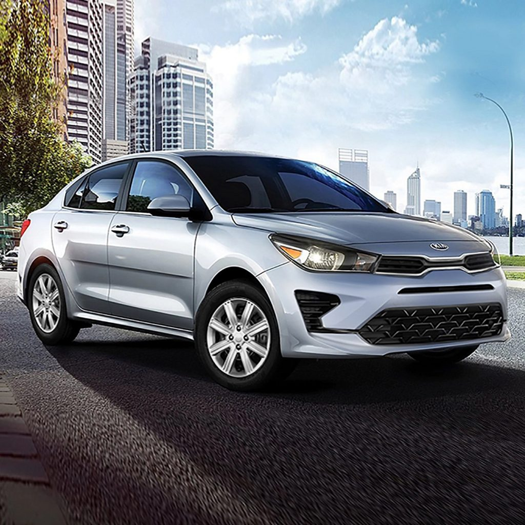 A silver 2021 Kia Rio with a city in the background.