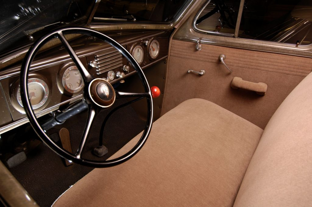 The interior of a 1937 Oldsmobile featuring its steering wheel, transmission, dashboard, and upholstery