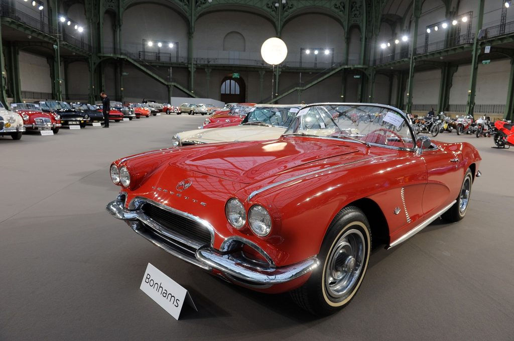 A red 1962 Chevrolet Corvette sitting in a large building with high ceilings with other classic cars.