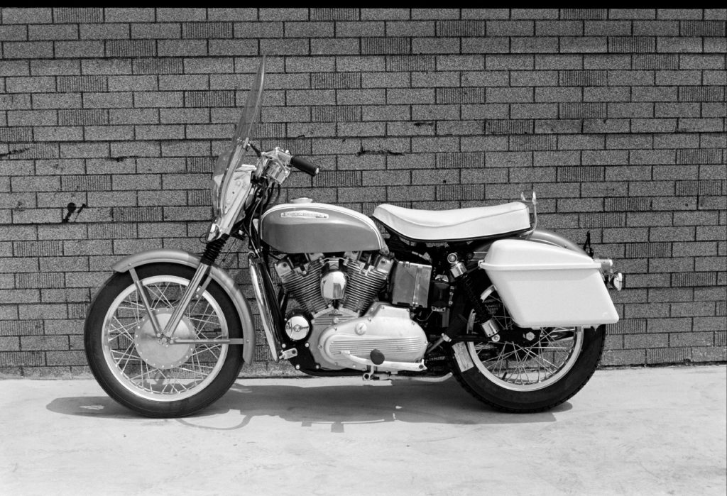 The side view of a 1967 Harley-Davidson XLH Sportster parked against a building