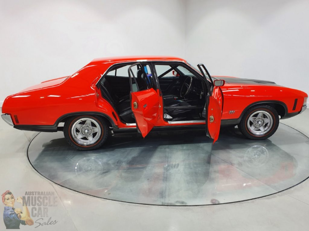 The side view of the liveried red-and-black 1972 Ford Falcon XA GTHO Phase IV prototype showing the full interior roll cage