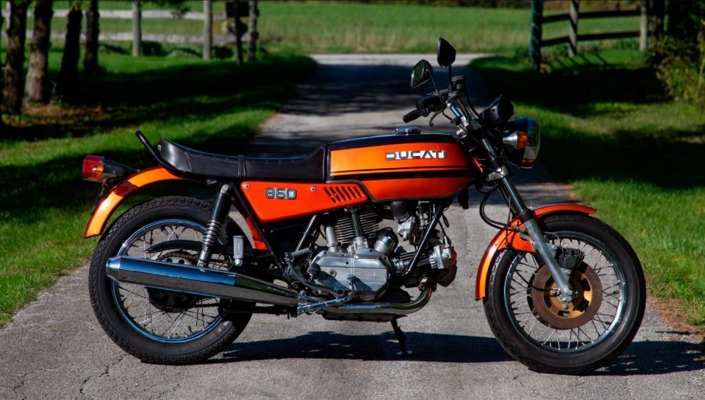 The side view of an orange 1975 Ducati 860 GT on a grassy dirt road