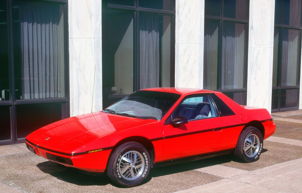 A red 1983 Pontiac Fiero in front of white pillars and a brown building lined with windows.