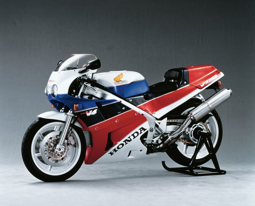A white-red-blue-and-black 1988 Honda VFR750R RC30 on a rear-wheel stand
