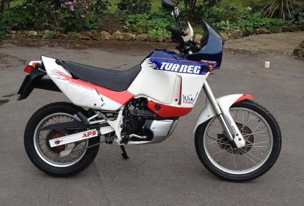 The side view of a white-red-and-blue 1989 Aprilia Tuareg Wind 600 in a parking lot