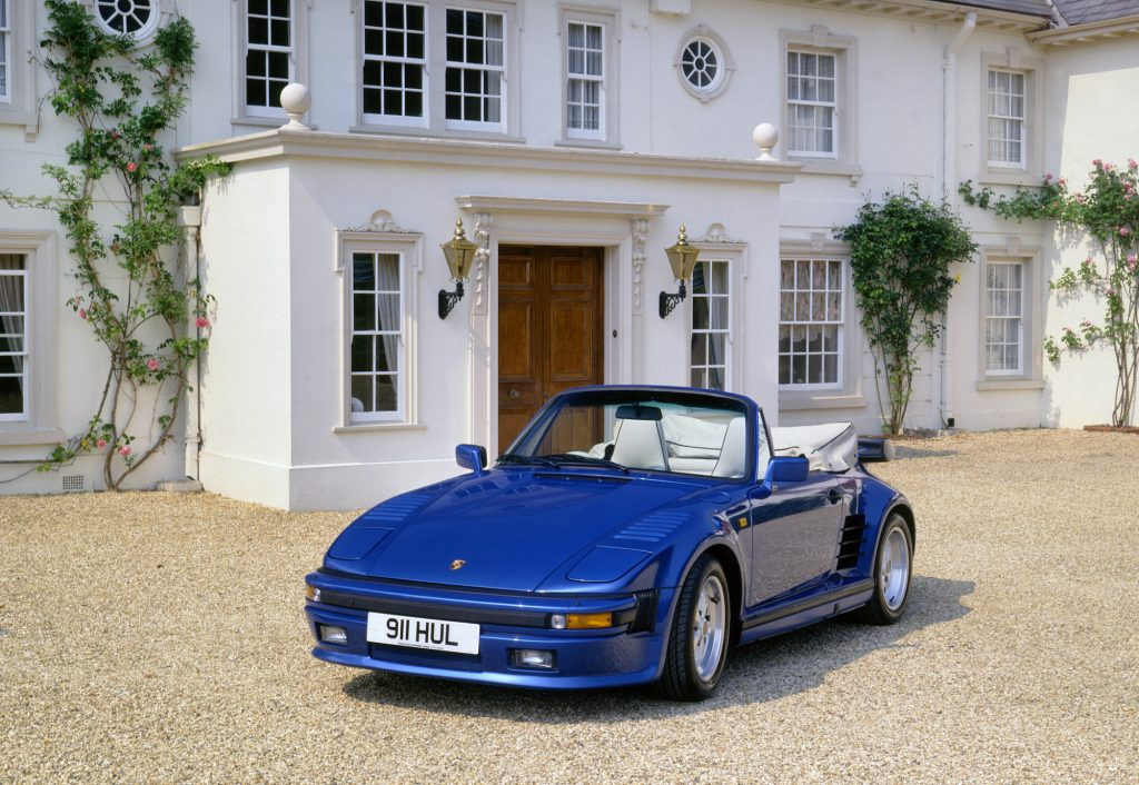 A royal-blue 1989 Porsche 911 Turbo SE Cabriolet parked in front of an ornate white building