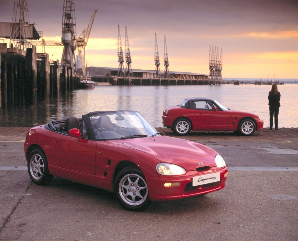 Two red 1991 Suzuki Cappucinos--one with its roof up, one with its roof down--next to a harbor