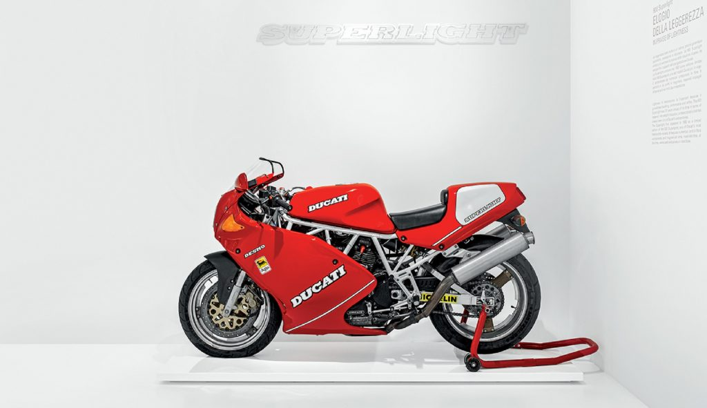 The side view of a classic red 1992 Ducati 900 SuperSport Superlight on a rear-wheel stand in the Ducati museum