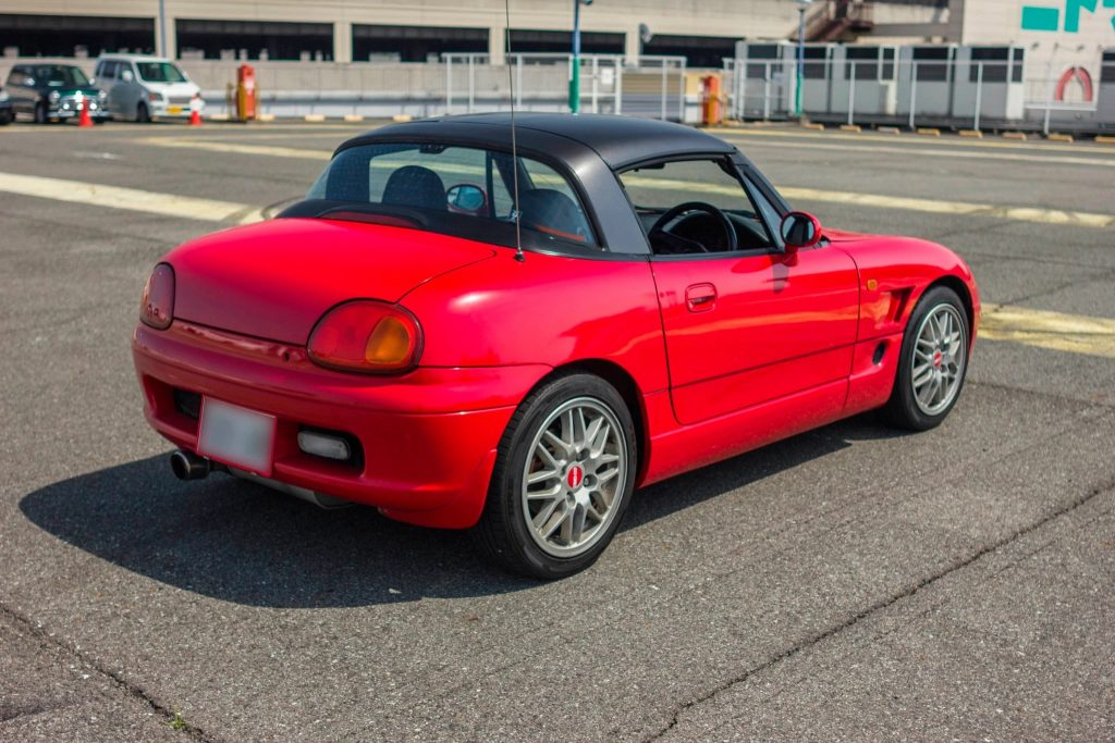 The rear 3/4 view of a red 1993 Suzuki Cappuccino with a black roof in a parking lot