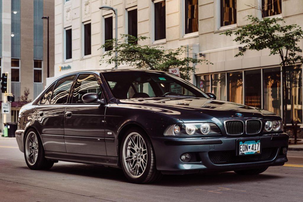 A blue-gray 2000 BMW E39 M5 on a city street
