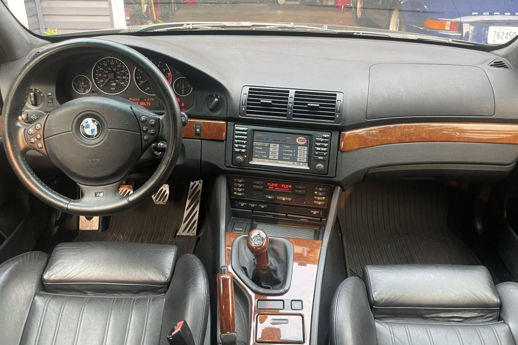 The black-leather-upholstered and wood-trimmed front seats and dashboard of a 2000 BMW E39 M5