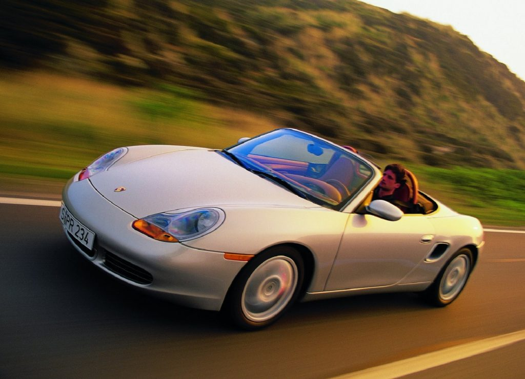 A silver 2001 Porsche Boxster S driving down a road ringed by hills