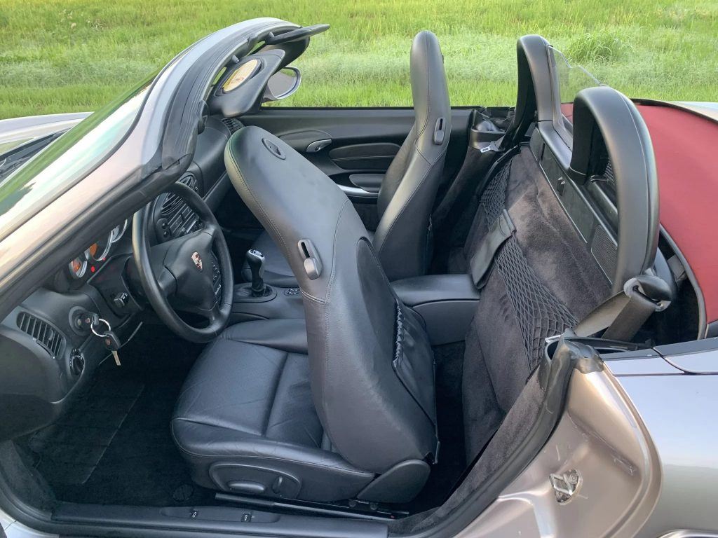 The side view of a tan-silver 2002 Porsche Boxster S's partial-black-leather interior