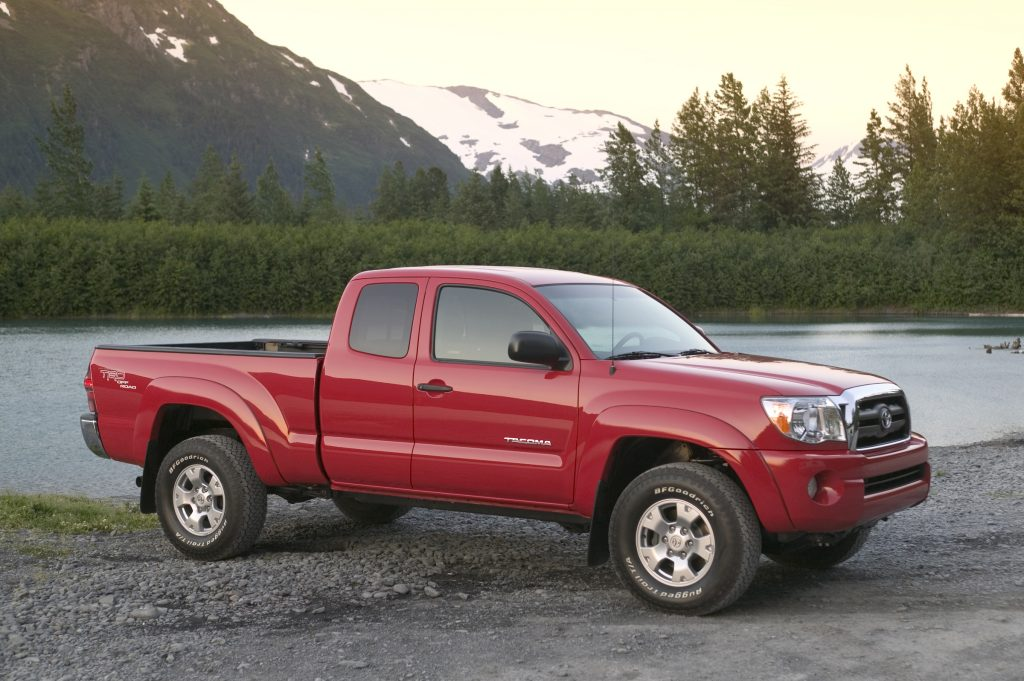 access cab used Toyota Tacoma from 2007 in a bright red color parked off-road near a lake with mountains