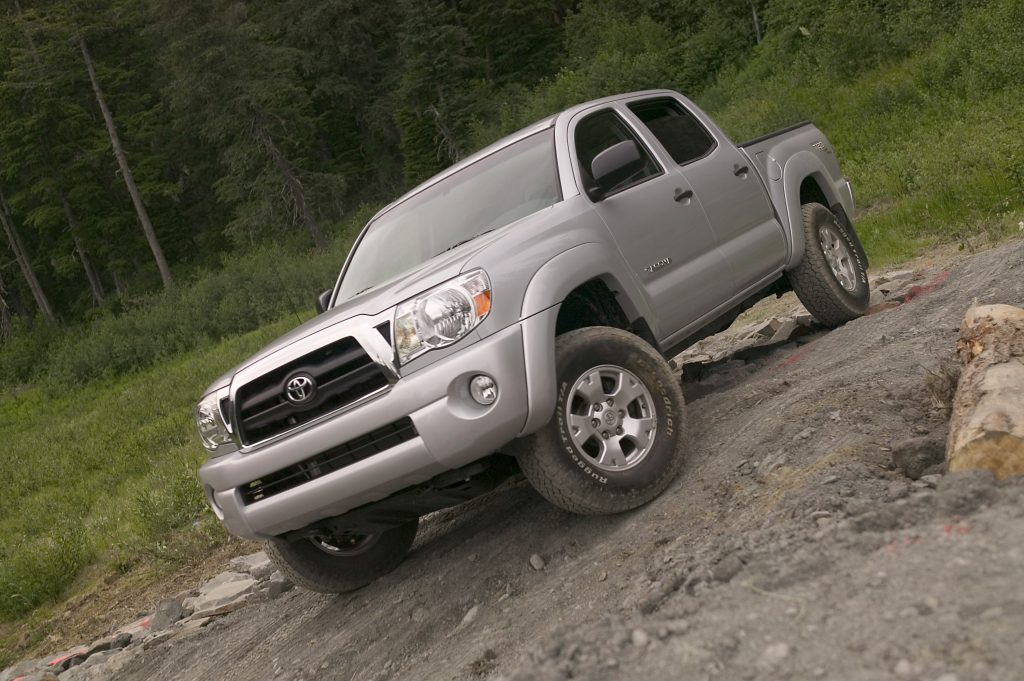 a silver 2007 used Toyota Tacoma driving off-road on a rocky trail
