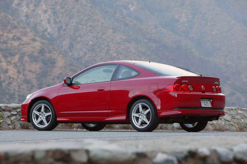 The rear 3/4 view of a red 2006 Acura RSX Type S on a canyon road