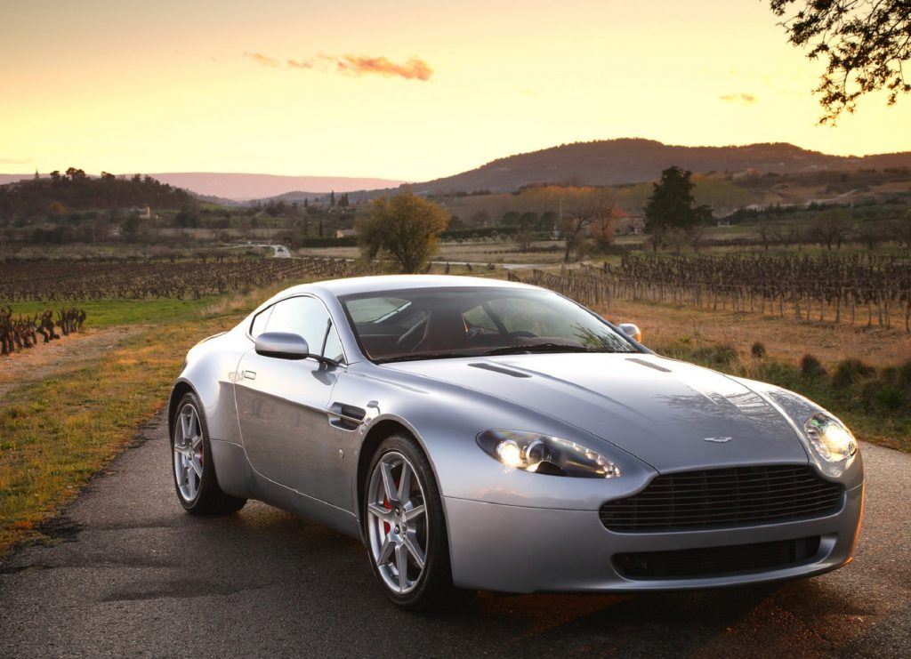 A silver 2007 Aston Martin V8 Vantage on a sunset country road