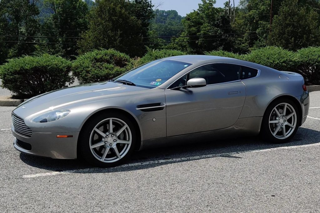 The side 3/4 view of a gray 2008 Aston Martin V8 Vantage in a parking lot