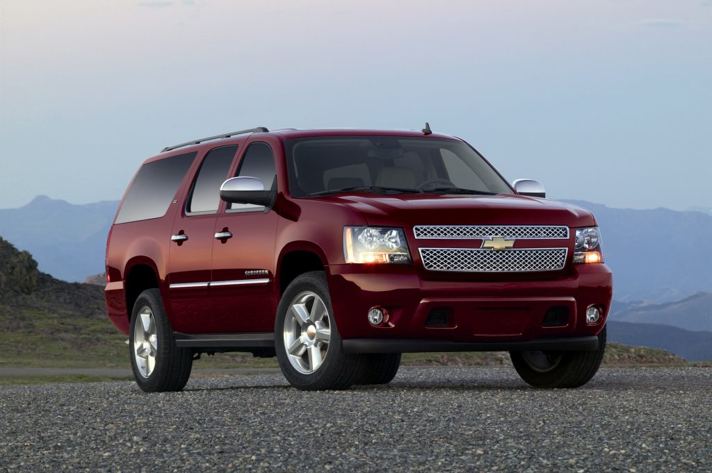 A burgendy 2011 Chevrolet Suburban LTZ full-size SUV parked on gravel in front of misty mountains