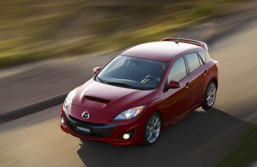 A red 2012 Mazdaspeed 3 photographed from a high angle while driving shows that its the perfect affordable used car that is also a killer sleeper car.