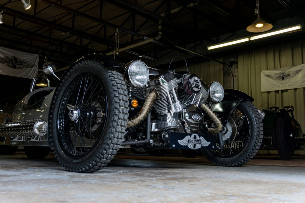 A low-angle front 3/4 view of a silver 2012 Morgan 3-Wheeler in a garage